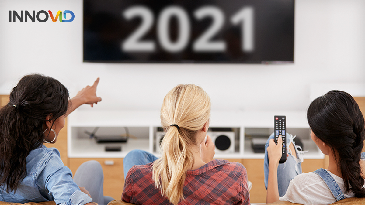 3 women, pointing at a TV. The TV has 2021 displayed on it.